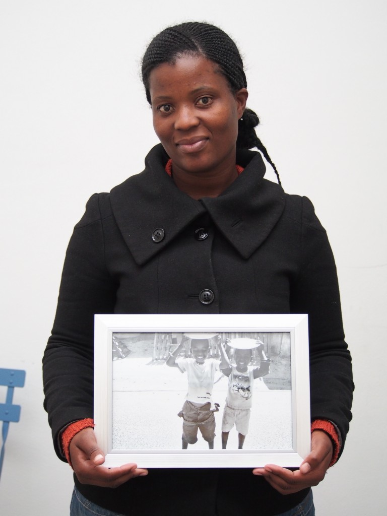 """Nwabisa Ndongeni, mother of 2 holds a 12""""x8"""" print of her 1.0 series postcard"""